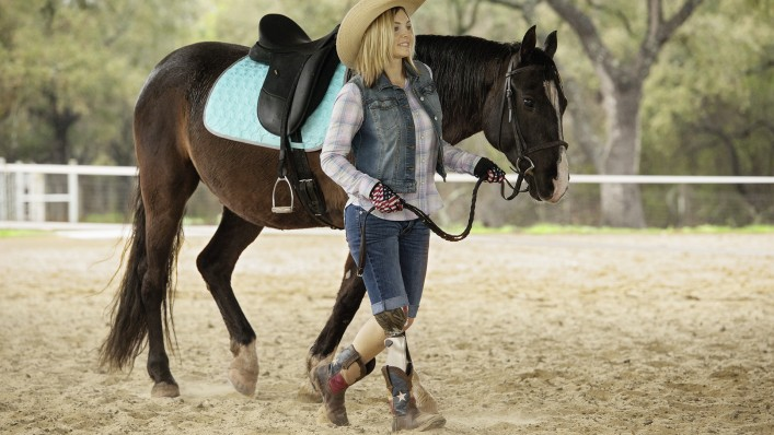 A cowgirl leads her horse across a riding ground. She wears a C-Leg on her right leg.
