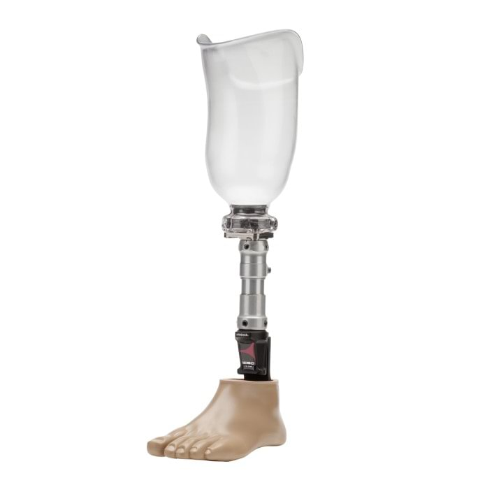 Transtibial prosthesis with transparent socket and 1C60 Triton prosthetic foot. The dynamic vacuum system is visible at the distal end of the socket (away from the body).