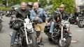 Georg stands between two Harleys, entirely relaxed as he laughs and poses for the camera.