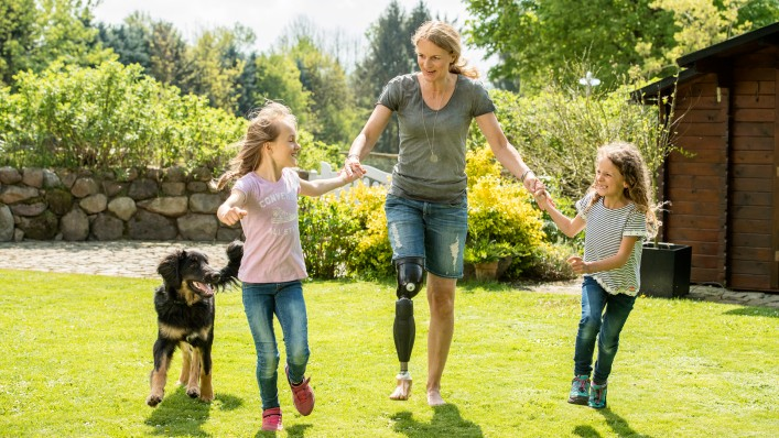 Genium X3 user Kerstin plays with her children and dog in the garden.