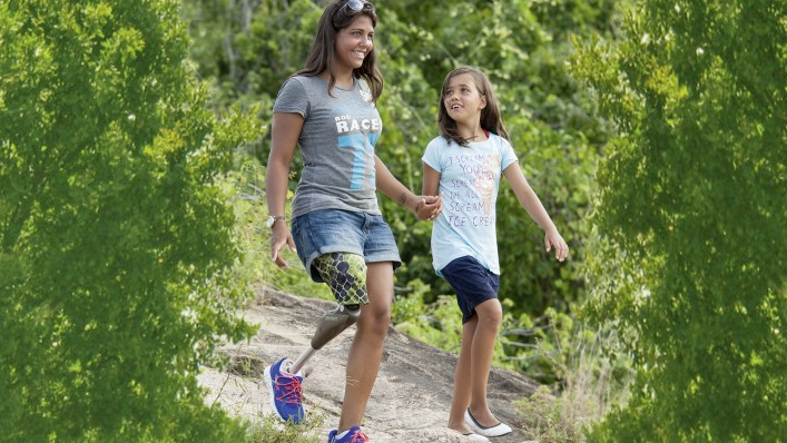 Karlianny walks downhill with her daughter