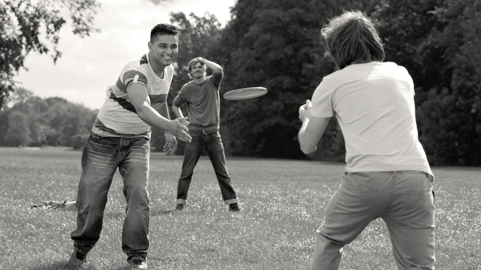 Hamed with Genium prosthesis playing frisbee with friends.