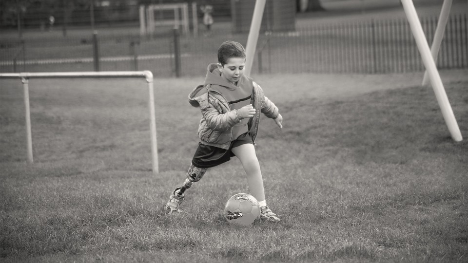 A young boy takes a big lunge with his prosthetic leg as he plays football on the pitch.