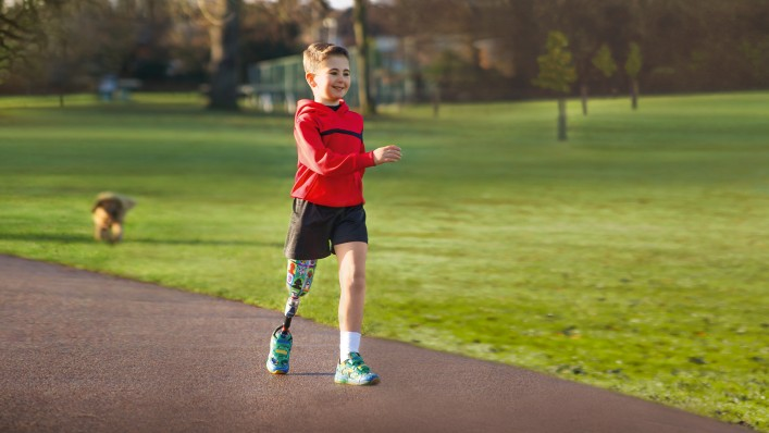 A young boy takes a running step on the footpath in the midst of a park.