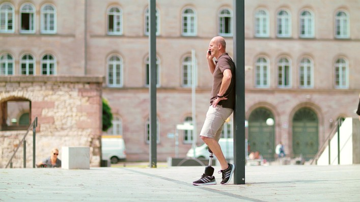 User Carsten stands relaxed against a lamppost while making a phone call; he is wearing the Empower Ankle prosthetic foot.