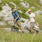 John and his friend hike through rough terrain