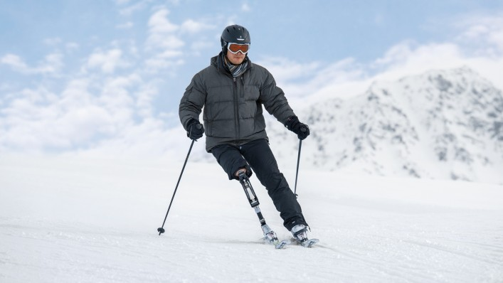 John enjoys the downhill tour on skis.