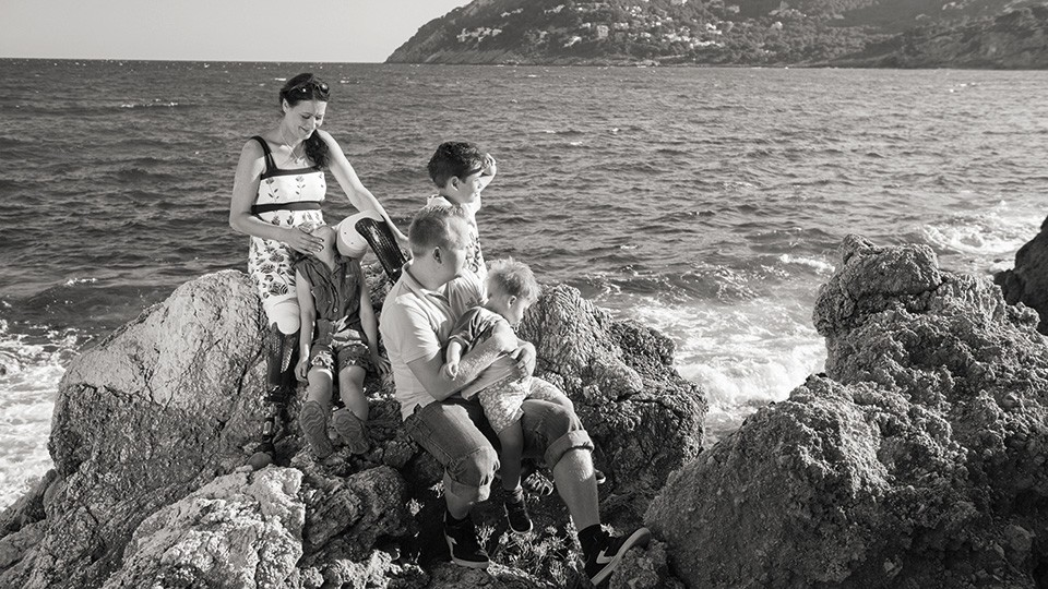 Bilateral amputee and Skeo user Myriam is shown sitting on a cliff with her family – the sea can be seen in the background.