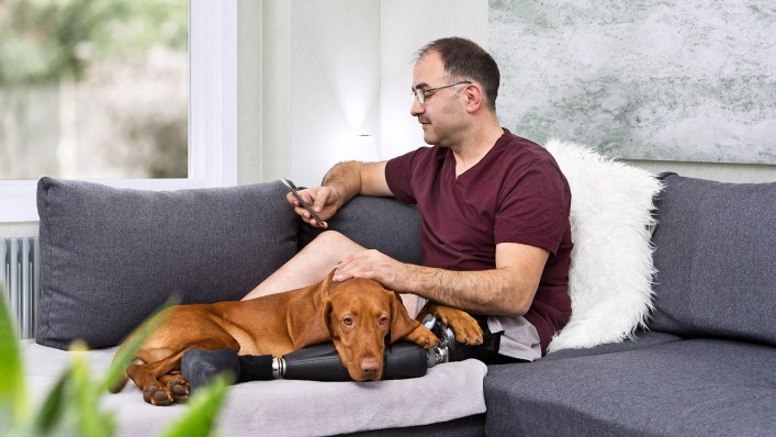 Feri rests on the sofa with his dog Kari lying on his prosthesis.