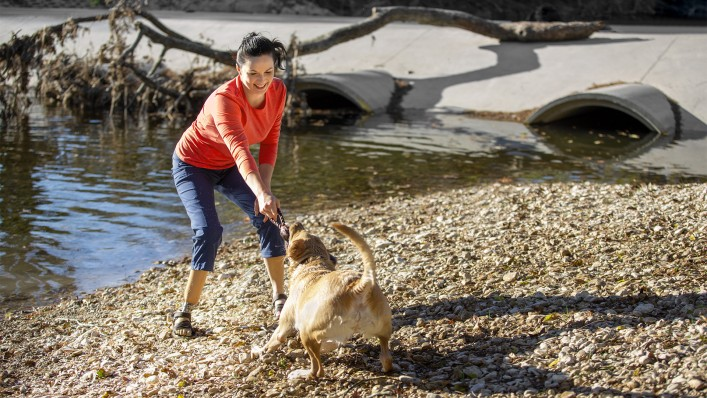Cassie wears her Taleo Low Profile prosthetic foot as she plays by the water with her dog.