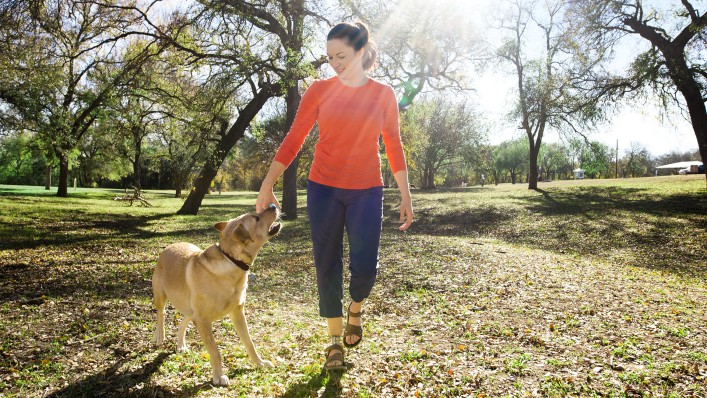 Cassie wears her Taleo Low Profile prosthetic foot as she walks her dog.
