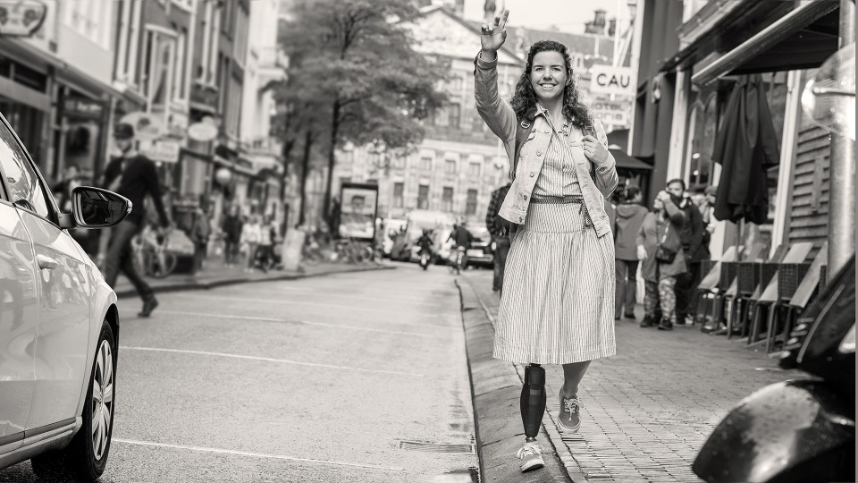 Marije waves at a taxi as she stands on the curb with her Triton side flex prosthetic foot.