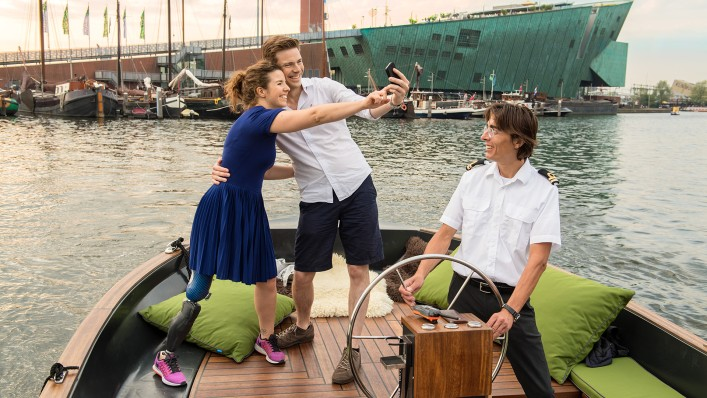 Marije and her boyfriend stand in the bow of a tourist boat, taking pictures of themselves with a smartphone