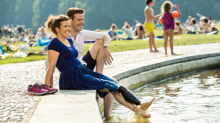 Marije and her boyfriend sit on the edge of a fountain and let their legs dangle in the water