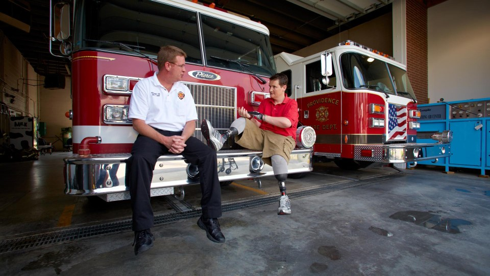 Neil at the fire station with his Harmony prosthetic legs.