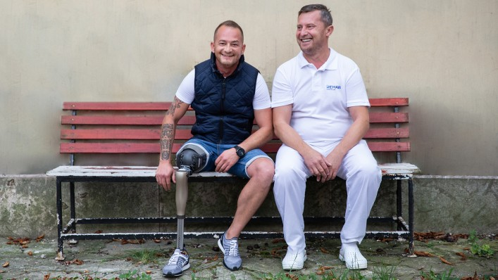 The image shows an O&P professional and a prosthesis wearer with the Varos socket. Both look cheerful and relaxed as they sit on a bench.