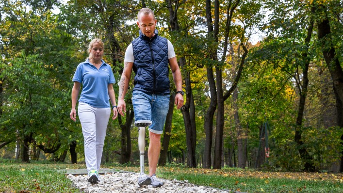 Image shows prosthesis wearer during physiotherapy session. He is walking on a special gait training route with a rocky, uneven surface.