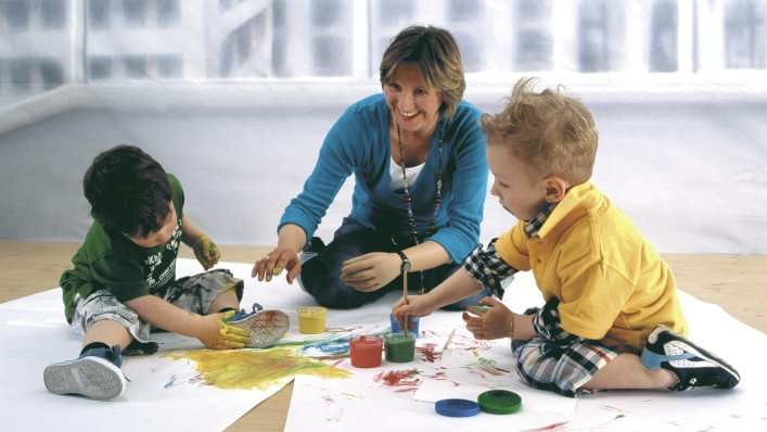 Young mother wearing SkinNatural prosthesis gloves and drawing with her children