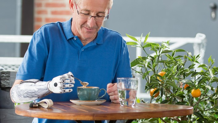 A bebionic prosthetic hand user stirring his cappuccino using the key grip.