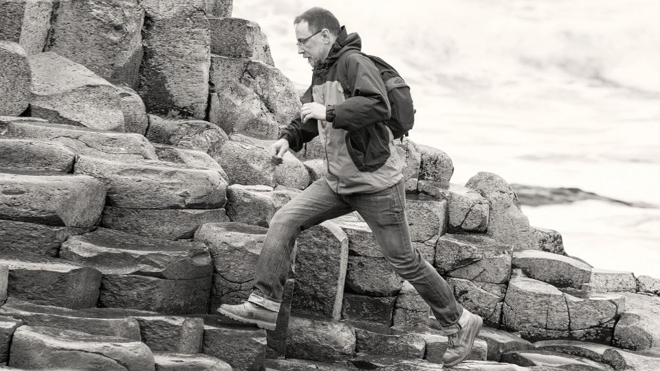 John walks over rocky ground with his prosthesis.