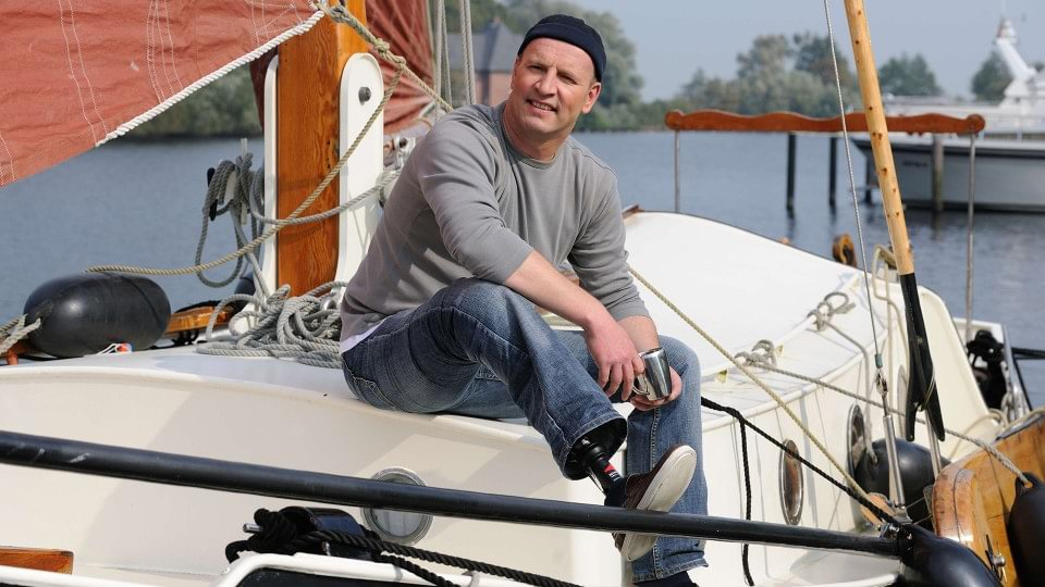 Carsten with Harmony prosthesis sitting on his sail boat.