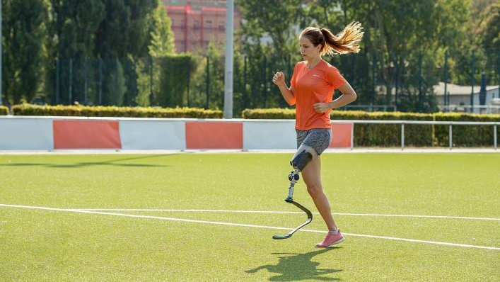 Female runner with sport prosthesis on a football pitch