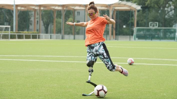 Female athlete plays football with a sport prosthesis