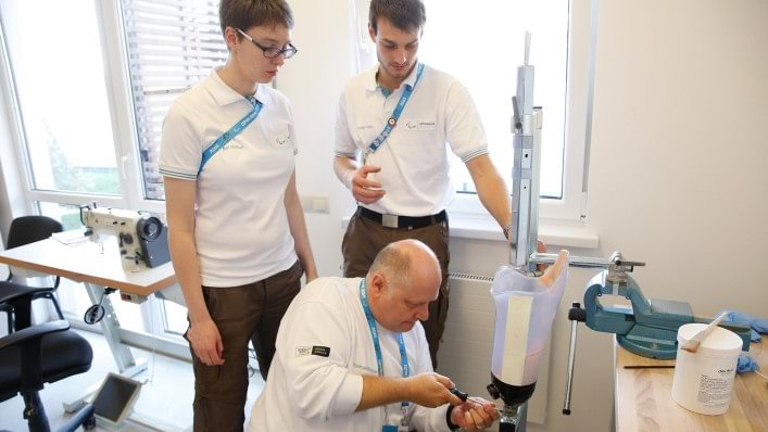Thomas Pfleghar, O&P professional and Ottobock Technical Director at the Rio 2016 Paralympic Games, works together with two colleagues to repair the socket of an athlete's leg prosthesis.