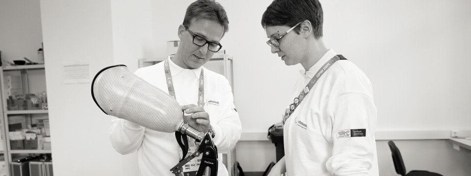 Peter Franzel, Organising Director of Ottobock's technical service for the Paralympic Games, discusses a repair to a ProCarve skiing and snowboarding prosthesis with an O&P professional.
