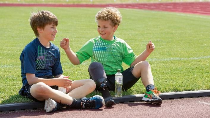 Child with prosthesis talks to his friend.