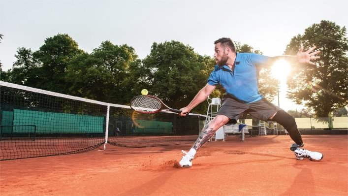 Tennis player playing the ball on his backhand.
