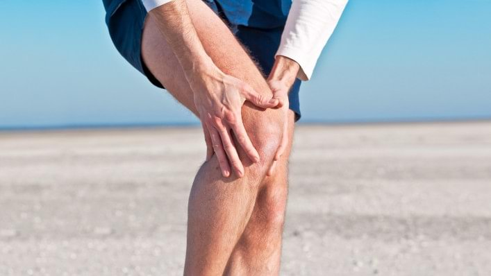 A man affected by osteoarthritis grips his right knee in pain.