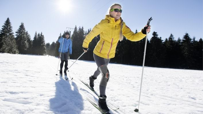 Woman affected by osteoarthritis skiing with the Agilium Patella brace