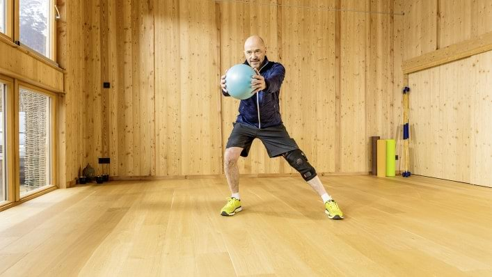 A person affected by osteoarthritis wearing Agilium Move performs movement exercises with a rubber ball.