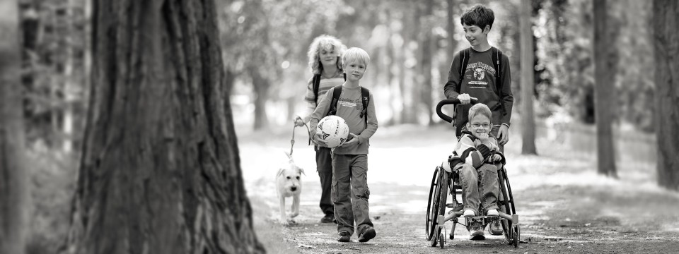 Children walking in the park with their friend who is in a Bravo Racer wheelchair.