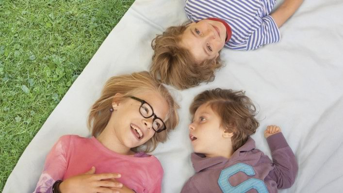 Three children laughing lying on a blanket on lawn.