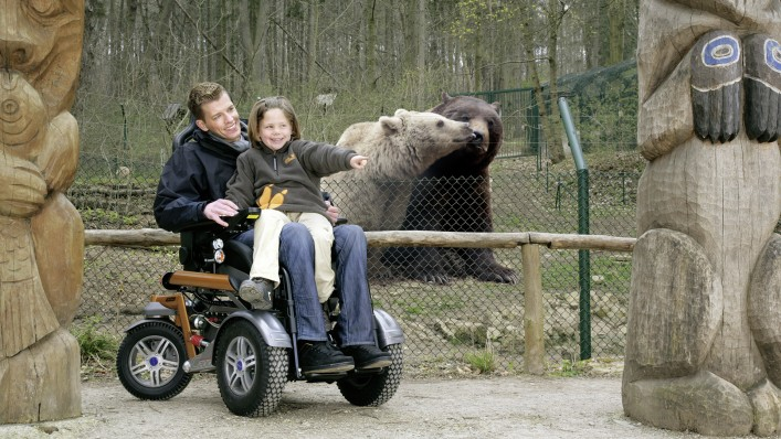 Man with a child sitting on his lap using a C2000 power wheelchair for a visit to the zoo