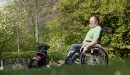 A man in his Start M5 wheelchair looking at his dog.