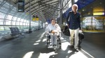 Marianne moving through an airport in her wheelchair with her husband