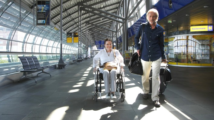Marianne in her wheelchair with her husband on an airport.