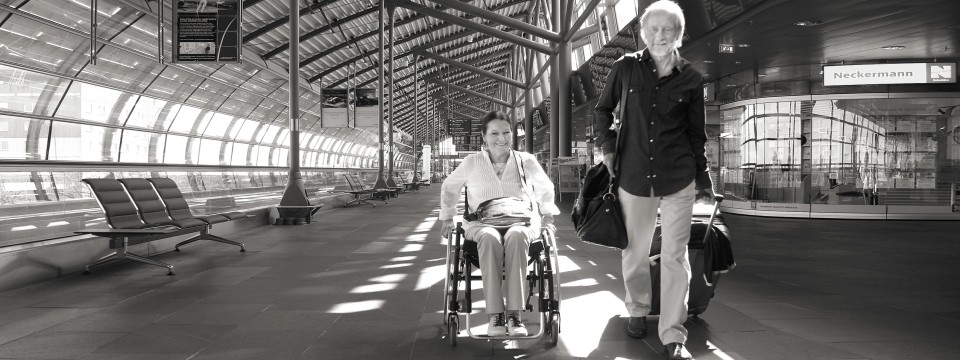 Marianne and her husband strolling through an airport while she is in her wheelchair