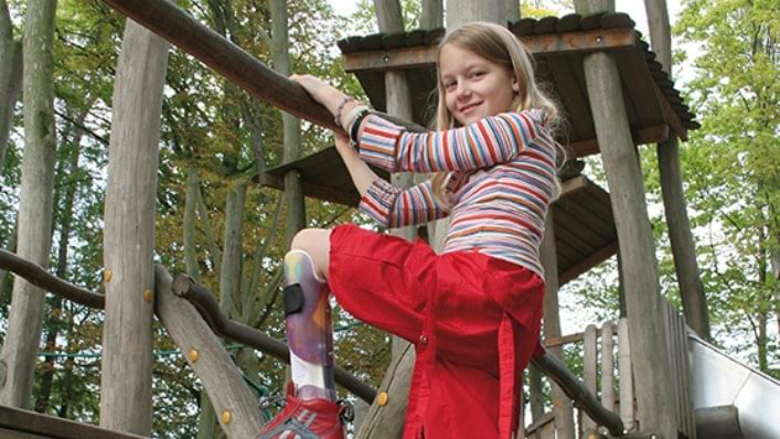 Girl climbing on a children's playground wearing an ankle foot orthosis.