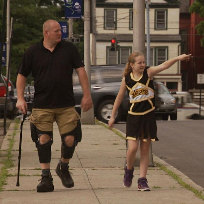Del walking with daughter using C-Braces.