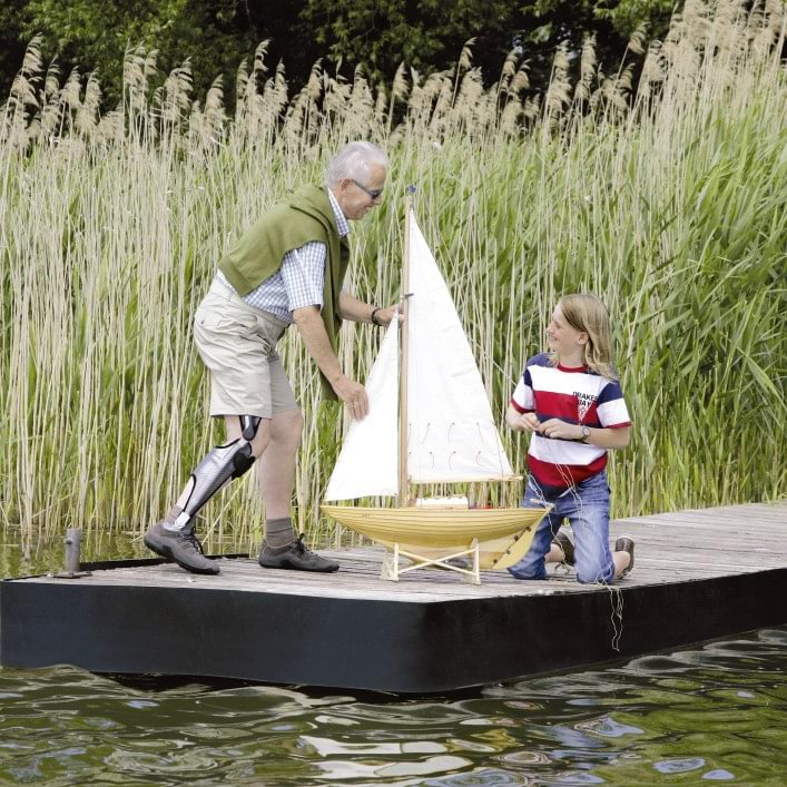 Peter with E-MAG Active orthosis and child playing with a sailboat.