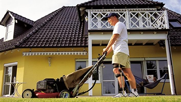 Man mowing the lawn wearing his Ottobock FreeWalk brace.
