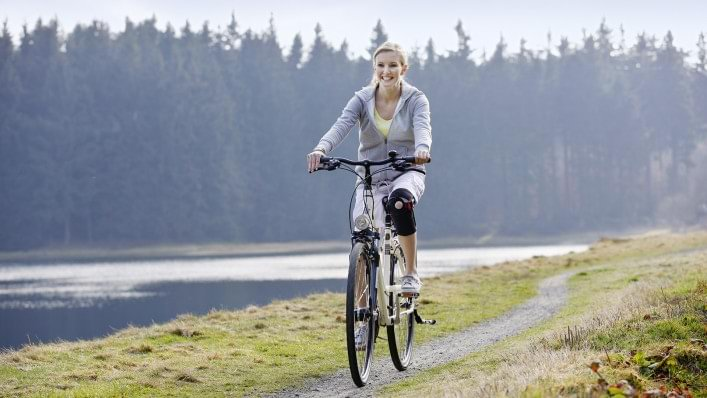 Woman riding a bike with the Patella Pro knee orthosis