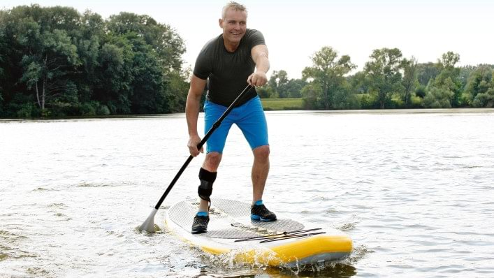 Henning riding a standup paddleboard while wearing a WalkOn brace