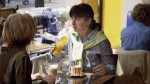 Daniela with DynamicArm sits in a cafe holding a glass of orange juice