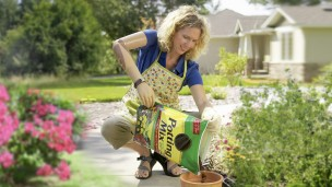 Sherri with DynamicArm prosthesis planting potted flowers.