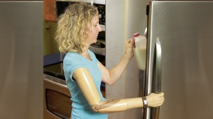 Sherri with DynamicArm prosthesis opening the door of the refrigerator to  put a milk bottle back.